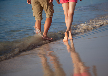 seacoast: Legs of a young man and woman walking along the seacoast Stock Photo