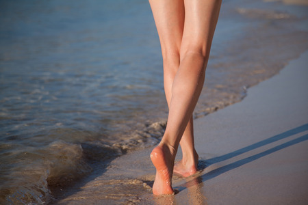 seacoast: Legs of a young woman walking along the seacoast