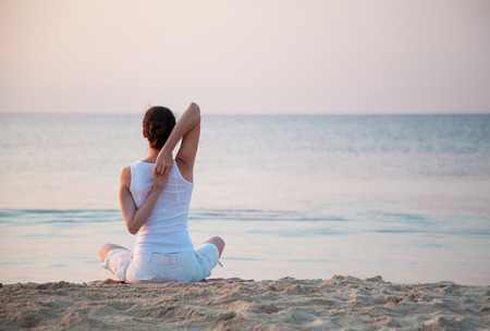 Young woman doing exercises sitting on sea coast at dawn
