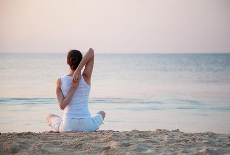 estilo de vida: Mulher que faz exercícios jovens sentados na costa de mar ao amanhecer