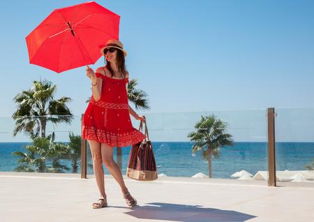dia soleado: Feliz mujer joven en un vestido rojo con un paraguas rojo en el fondo marítimo Foto de archivo