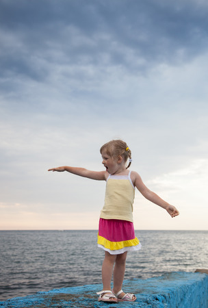 shouting girl: Pretty little girl standing on the embankment on sea background Stock Photo