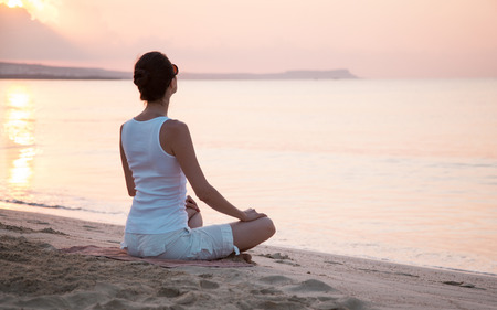 Young woman meditating on the sea coast at dawn