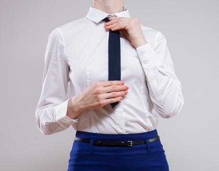 neutral background: Unrecognizable businesswoman sets the necktie on neutral background Stock Photo