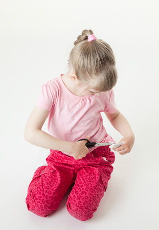snipping: Little girl snipping off a brand label, white background
