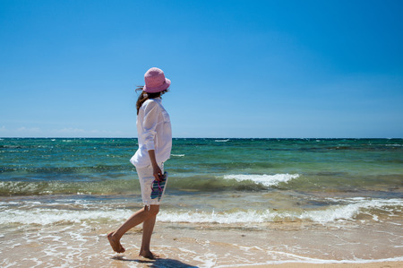 Young woman in white clothes walking along the seashore photo