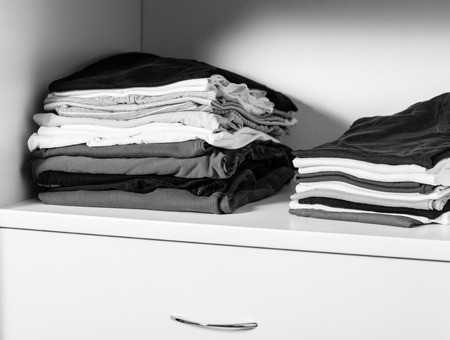 informal clothes: Casual clothes in a wardrobe - monochrome image Stock Photo