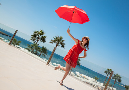 lighthearted: Happy young woman in a red sundress with a red umbrella on seafront background