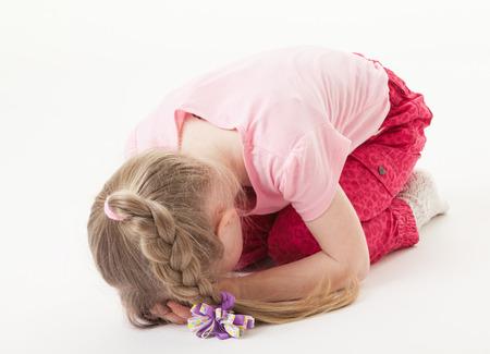 sorrowful: Sorrowful little girl on the floor, white background