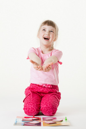 upgrowth: Happy little girl sitting on the floor, reaching out her palms and catching something, white background Stock Photo