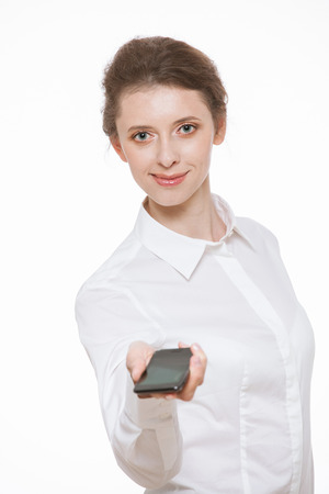 demonstrate: Beautiful young business woman holding mobile phone, white background