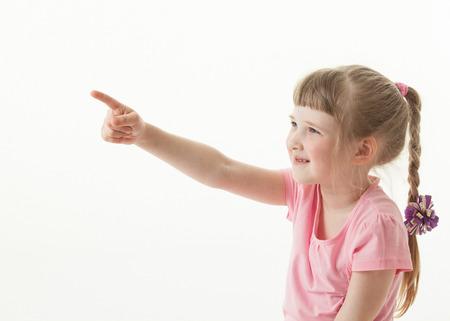 devise: Smiling little girl indicating something, white background