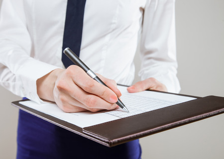 neutral background: Unrecognizable young businesswoman  holding documents and a pen, neutral background