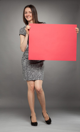 Young woman in dress  holding blank placard showing at it, full length portrait on gray background photo