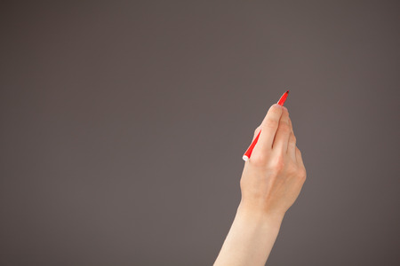 upgrowth: Female hand holding a red felt-tip pen on gray background