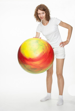 fitball: Smiling young woman doing exercises with big fitball on white background