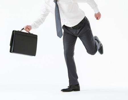 hasten: Unrecognizable young businessman running with a briefcase , white background Stock Photo