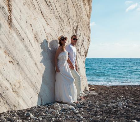 seacoast: Beautiful young couple near the rock on the seacoast