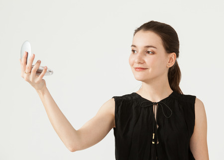 preen: Smiling young woman looking at herself in the mirror, white background