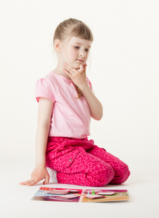 upgrowth: Pretty little girl sitting on the floor and thinking about game, white background Stock Photo