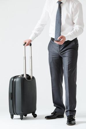 Onherkenbare zakenman met een mobiele telefoon en een koffer, witte achtergrond