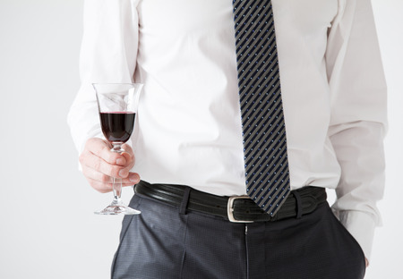 solemnize: Young businessman holding a goblet of wine, neutral background