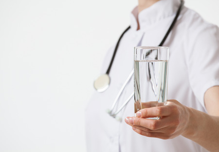 Doctor holding a glass with water, white background