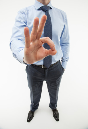 assent: Unrecognizable businessman showing a gesture OK, white background