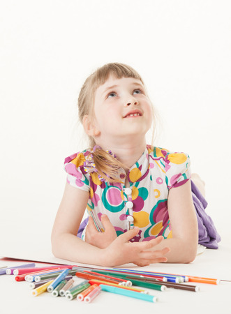 upgrowth: Smiling little girl lying on the floor and thinking, white background Stock Photo