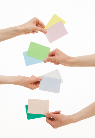 four hands: Four hands holding colorful paper cards, white background Stock Photo