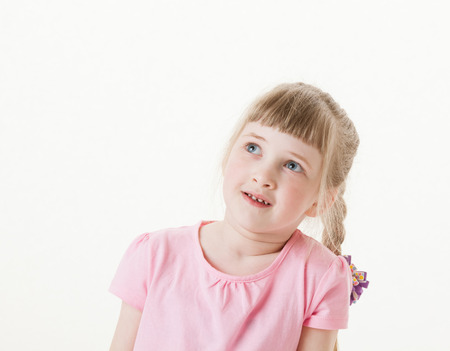 upgrowth: Portrait of a happy  pretty little girl looking up on white background Stock Photo