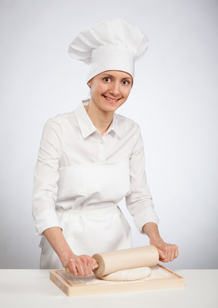 cook out: Beautiful young female cook rolling out dough on wooden board, gray background Stock Photo