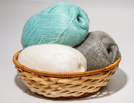 acrylic yarn: Skeins of yarn in a wooden basket on neutral background