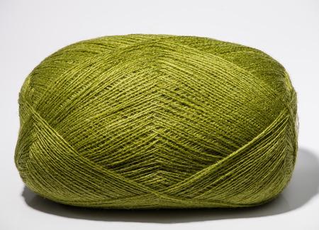 neutral background: One skein of green yarn on neutral background