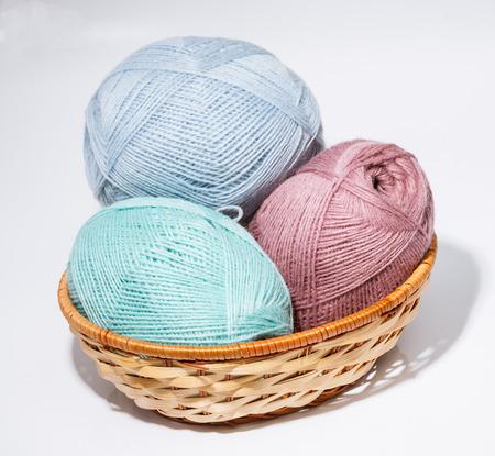 neutral background: Woolen yarn in a braided basket on neutral background Stock Photo