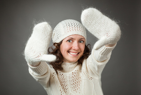 young add: Portrait of happy young woman in white hat and mittens, gray background