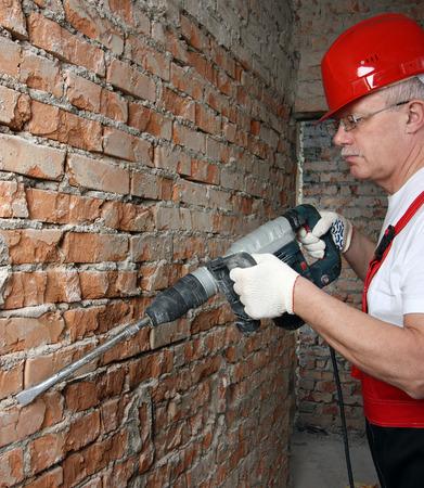 casco rojo: Constructor en uniforme y casco rojo trabaja con un plugger contra la pared de ladrillo