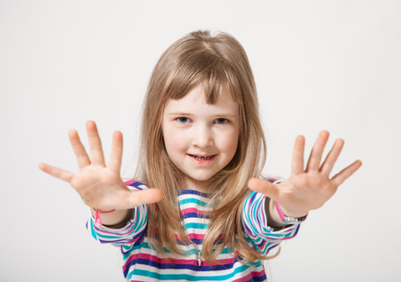 neutral background: Pretty little girl showing her palms, neutral background