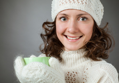 to get warm: Beautiful girl feeling cold and holding a cup of hot drink, grey background