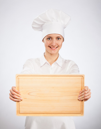 toque blanche: Smiling woman chef cook holding wooden board on neutral  background