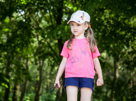 brushwood: Pretty little girl holding brushwood, natural green background