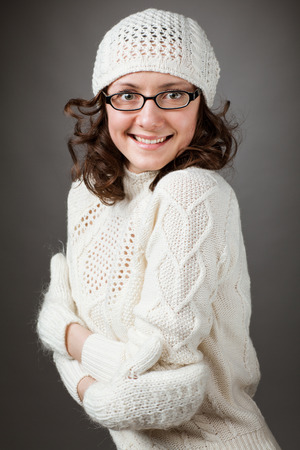 to get warm: Portrait of a beautiful young smiling brunette wearing chochet hat and mittens trying to get warm