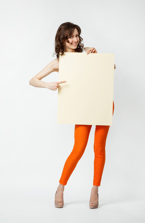 Playful young woman in orange pants holding blank placard showing at it, full length portrait on neutral background photo