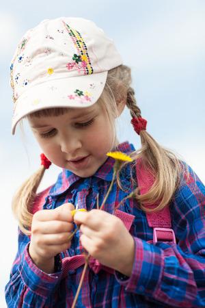 Pretty little girl tells fortunes by daisy