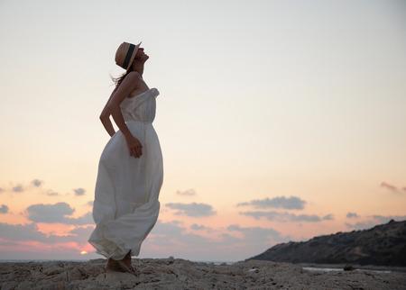 chapeau de paille: Bonne jeune femme se réjouit de vacances d'été et répond à un coucher de soleil