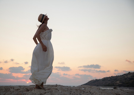 good evening: Happy young woman  rejoices at summer vacation and meets a sunset Stock Photo