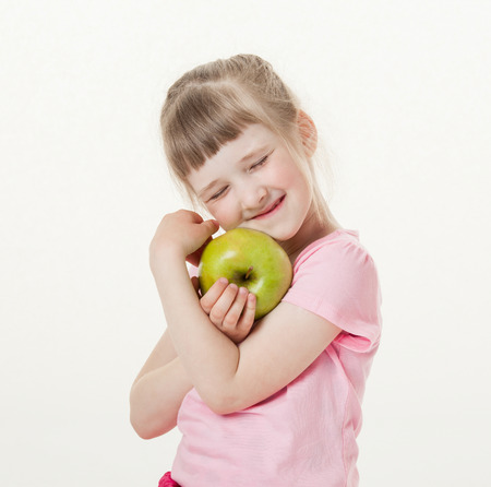 upgrowth: Happy little girl holding a green apple, white background