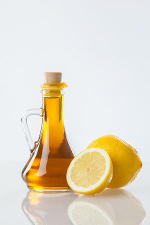 aceite oliva: El aceite de oliva y lim�n fresco en el fondo blanco Foto de archivo