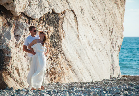 Beautiful young couple near the rock on the seacoast