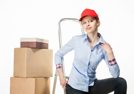 stepladder: Young woman sitting on the stepladder near the stack of boxes, white background Stock Photo